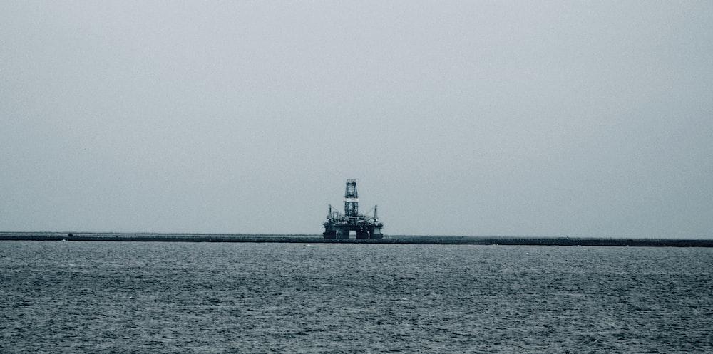 black ship on sea under white sky during daytime