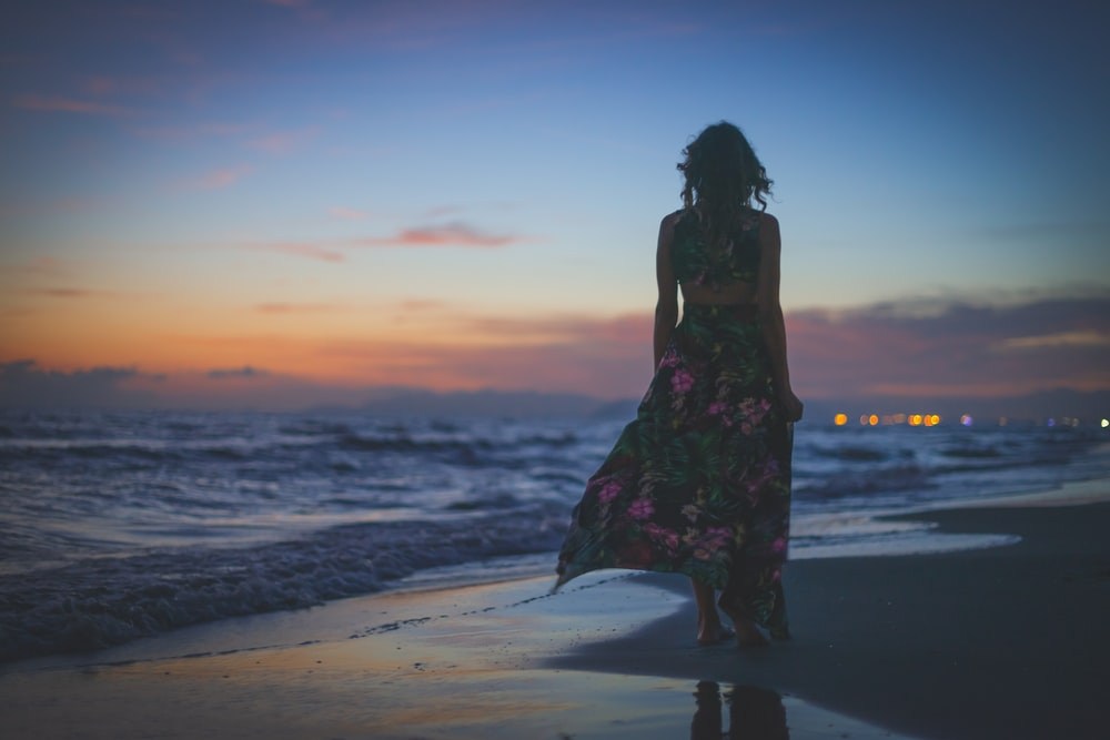 woman in black and red floral dress standing on beach during sunset