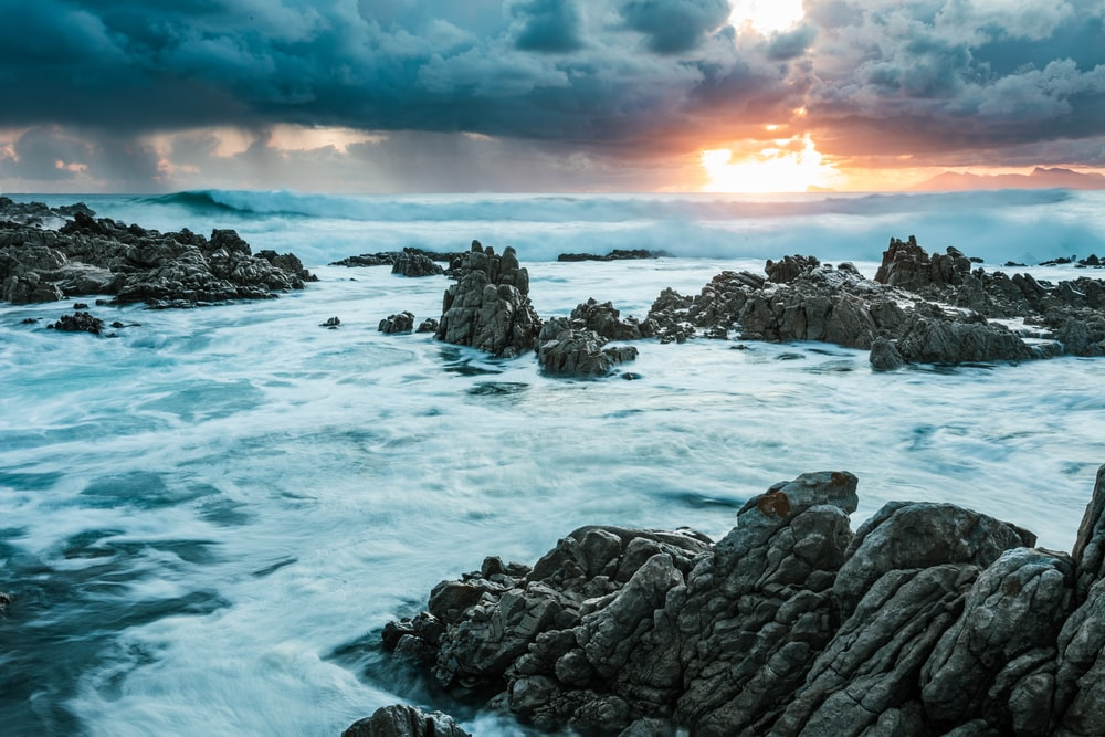 rocky shore with ocean waves during sunset