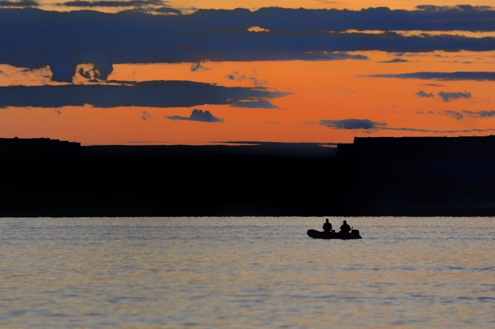 silhouette of two people riding on boat during sunset