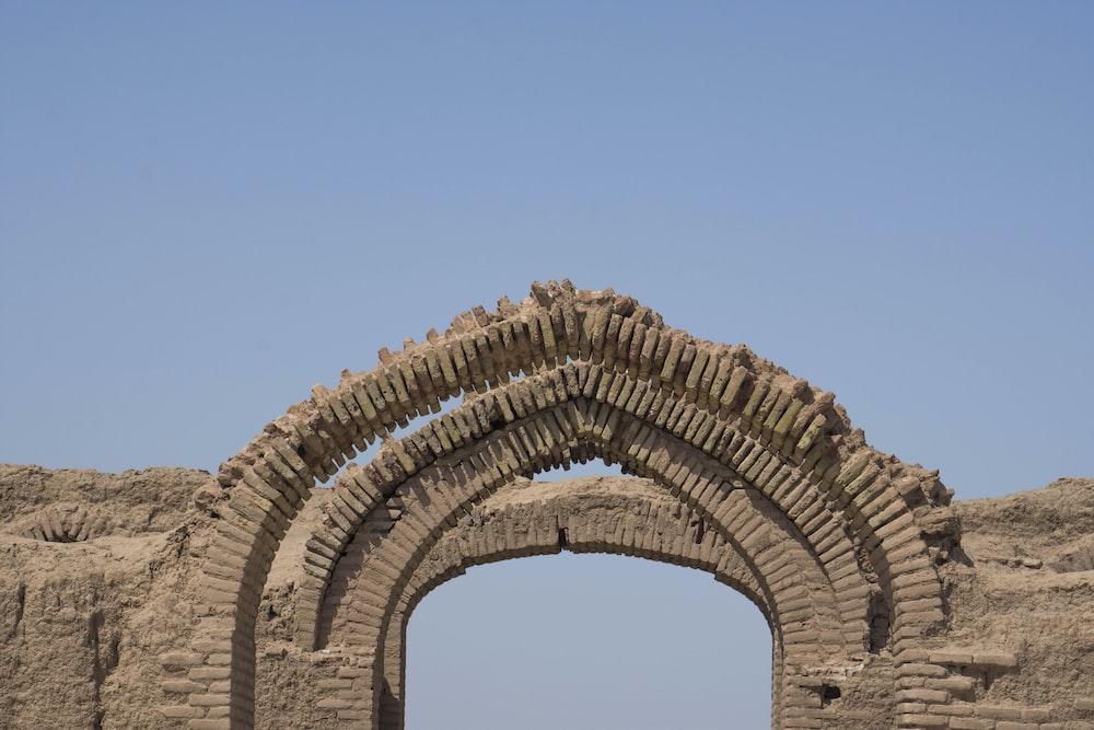 brown brick arch under blue sky during daytime