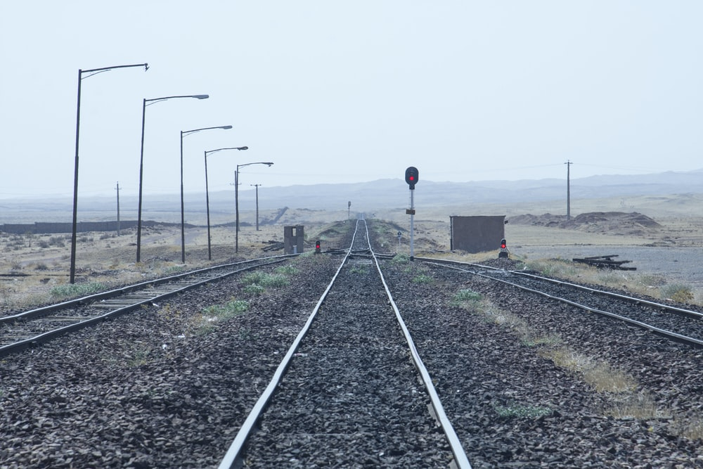 person in black jacket standing on train rail during daytime