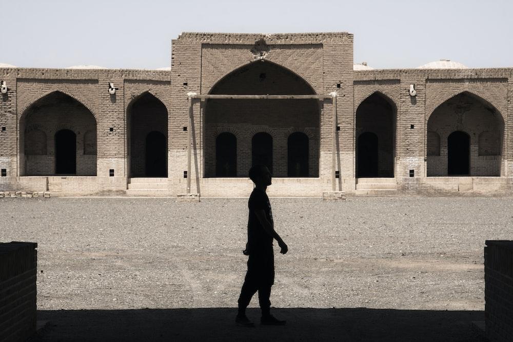 man in black coat walking on brown sand during daytime