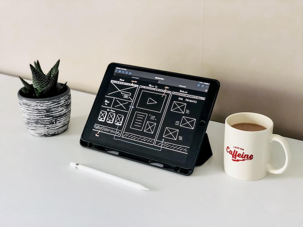 black ipad beside white ceramic mug on white table