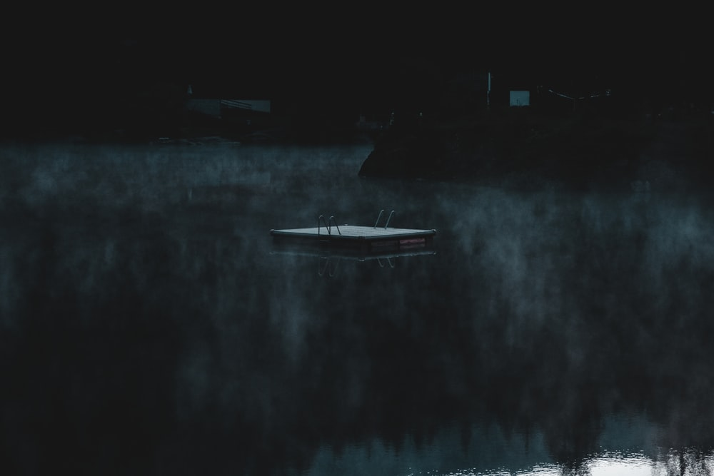 white boat on body of water during night time
