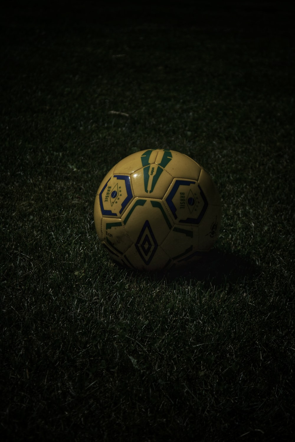 yellow and black soccer ball on green grass