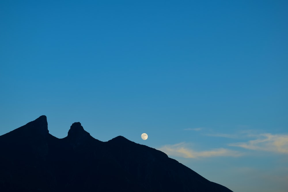 silhouette of mountain under blue sky during night time