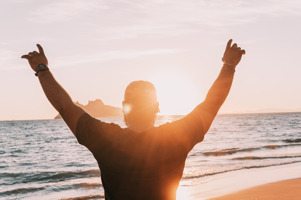 man in black shirt raising his hands on beach during daytime