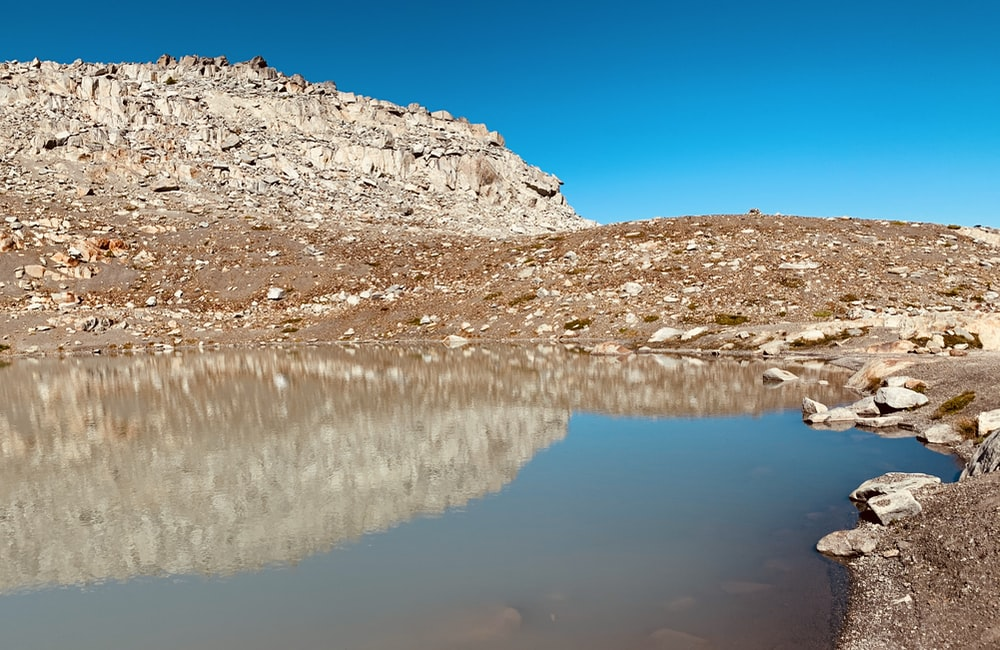 brown and white rocky mountain beside body of water under blue sky during daytime