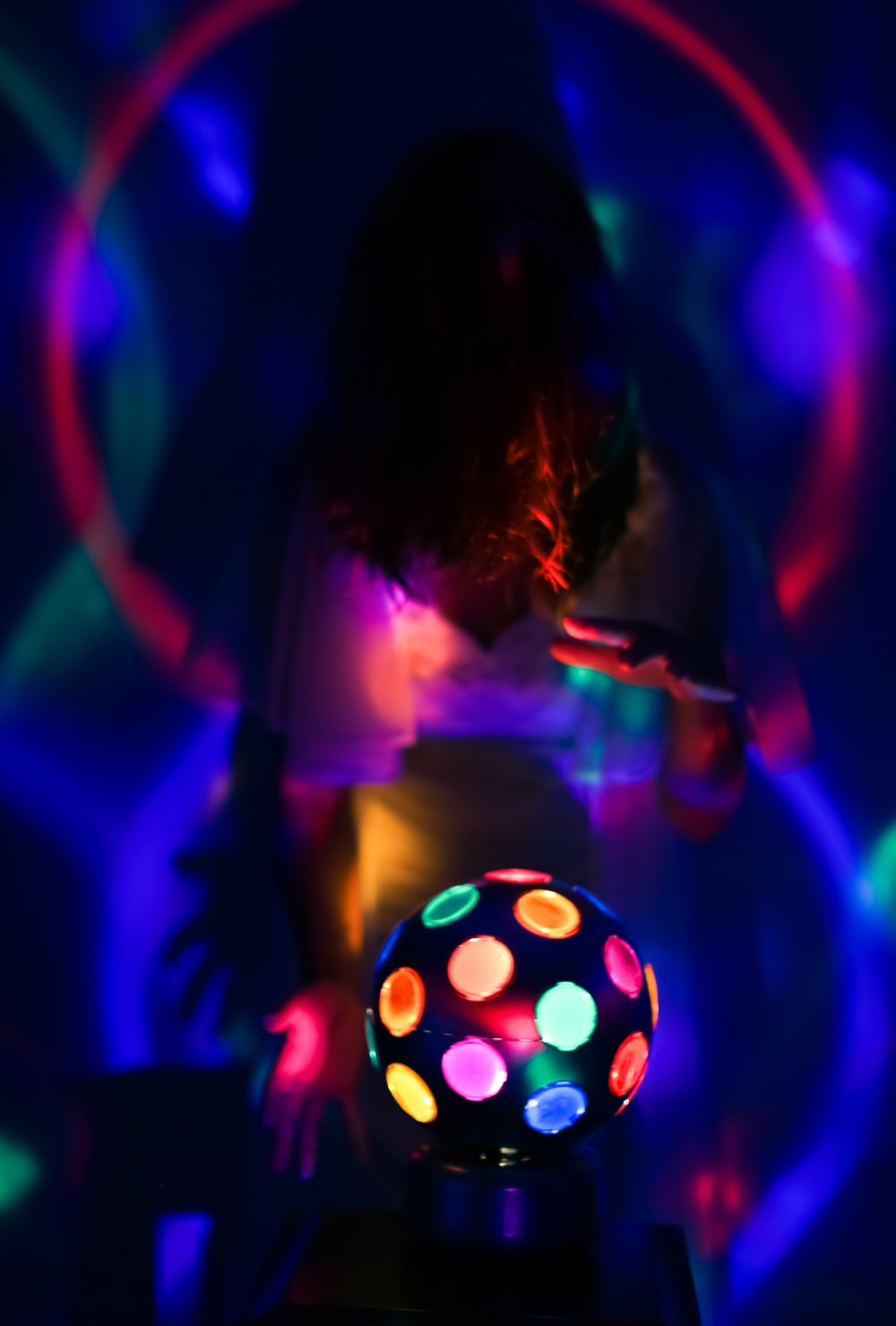 girl in pink shirt playing with lighted ball