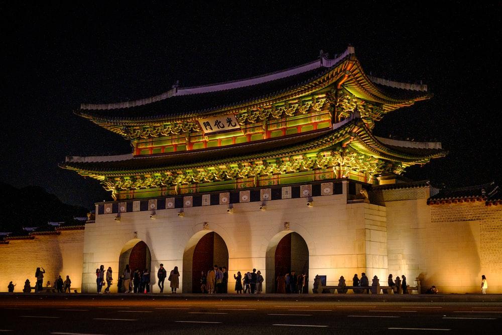 people walking near brown concrete building during nighttime