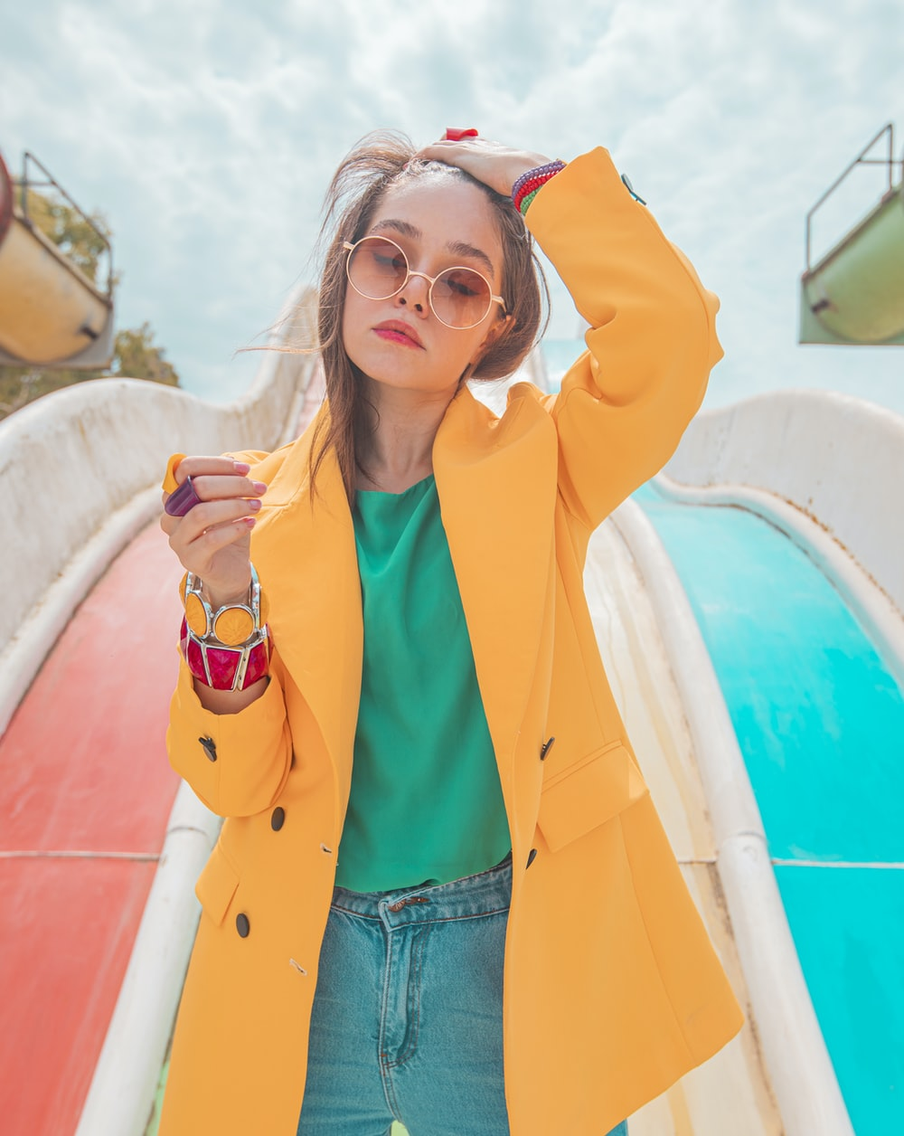 woman in yellow jacket and blue denim shorts holding white and red ceramic mug