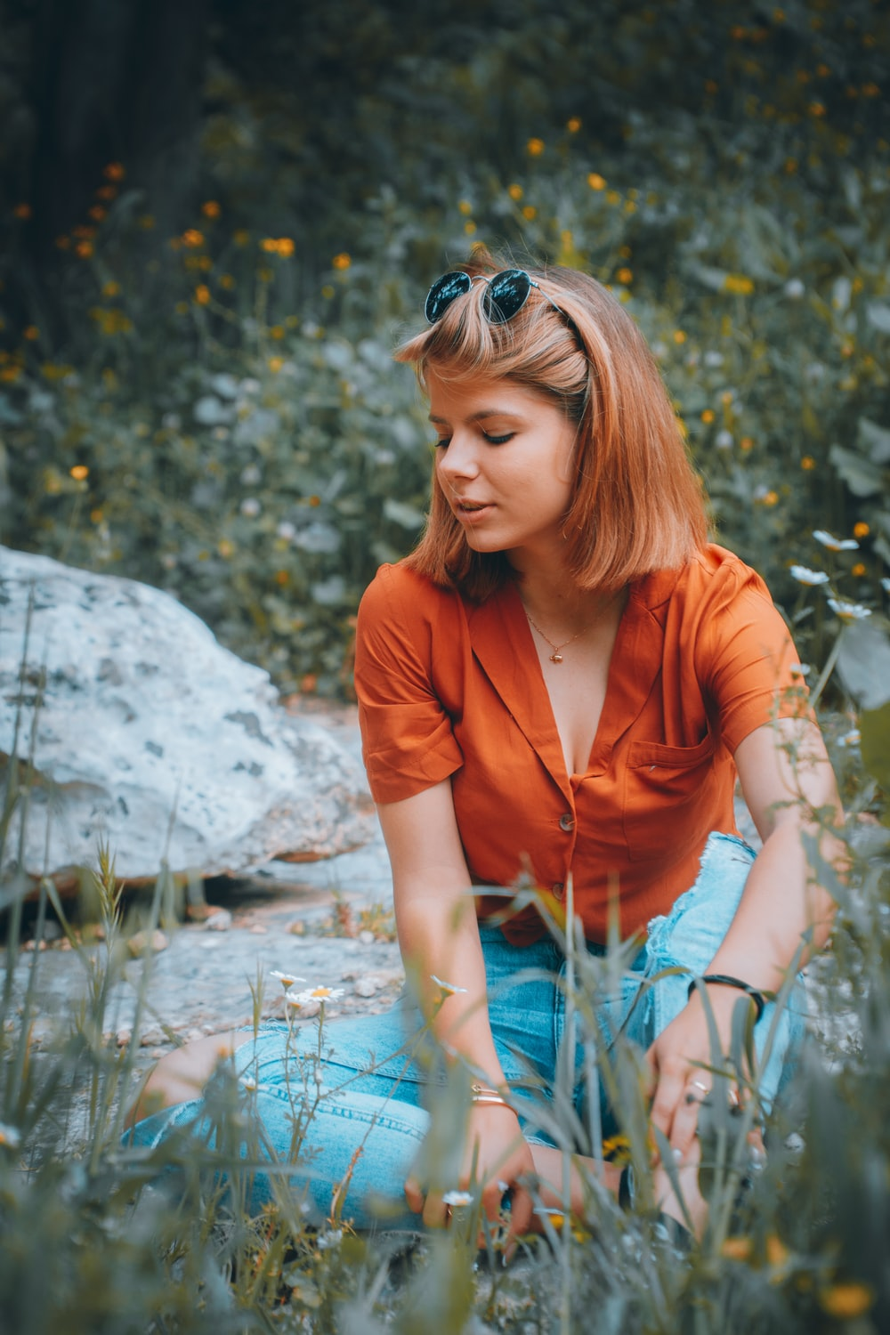 woman in orange button up shirt wearing blue sunglasses sitting on rock in river during daytime