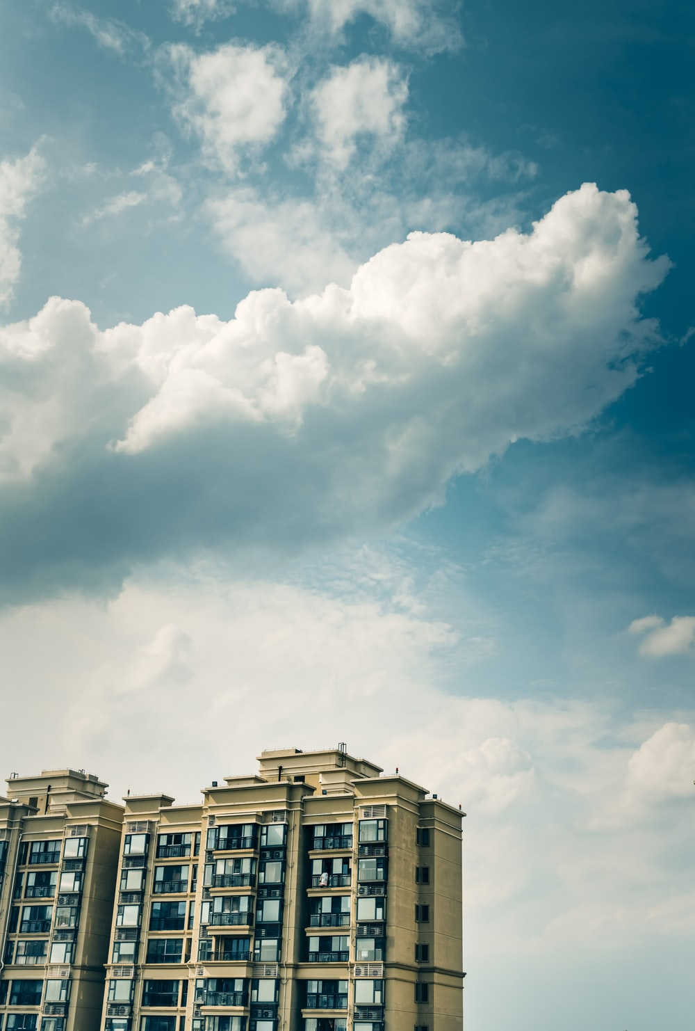 white and brown concrete building under white clouds and blue sky during daytime
