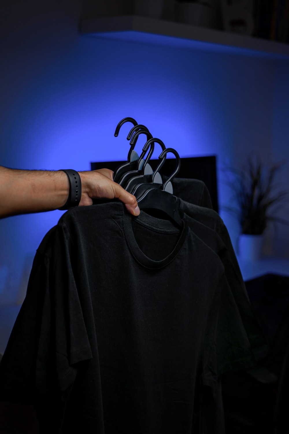 person holding black textile with blue light