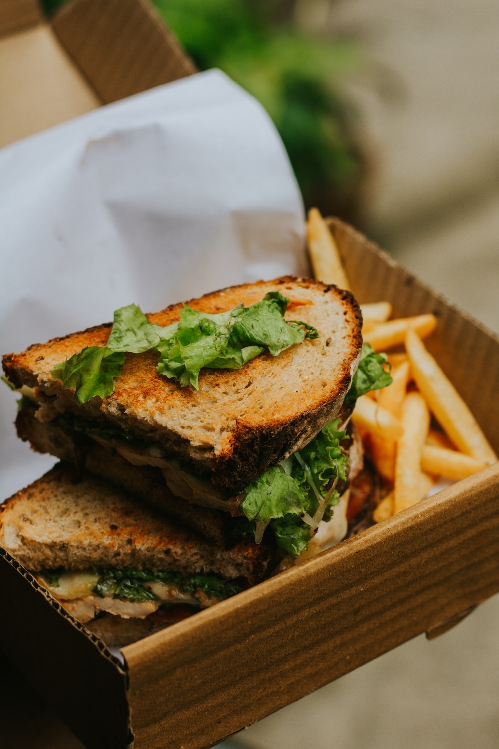 burger with lettuce and fries on brown wooden tray