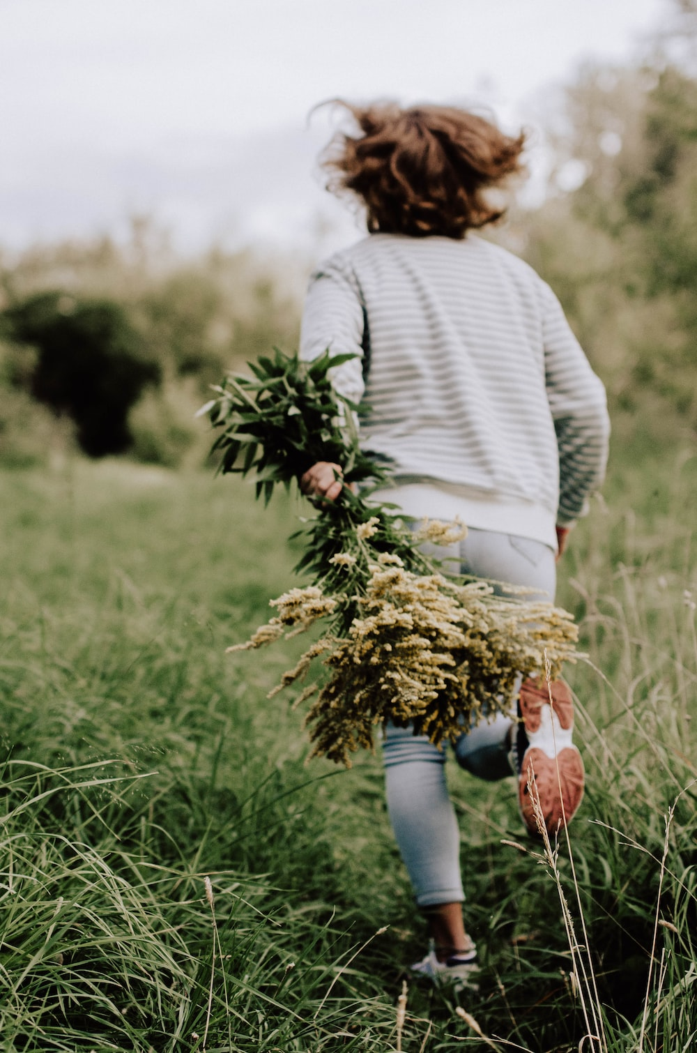 woman in green sweater and blue denim jeans holding brown basket with brown and green grass