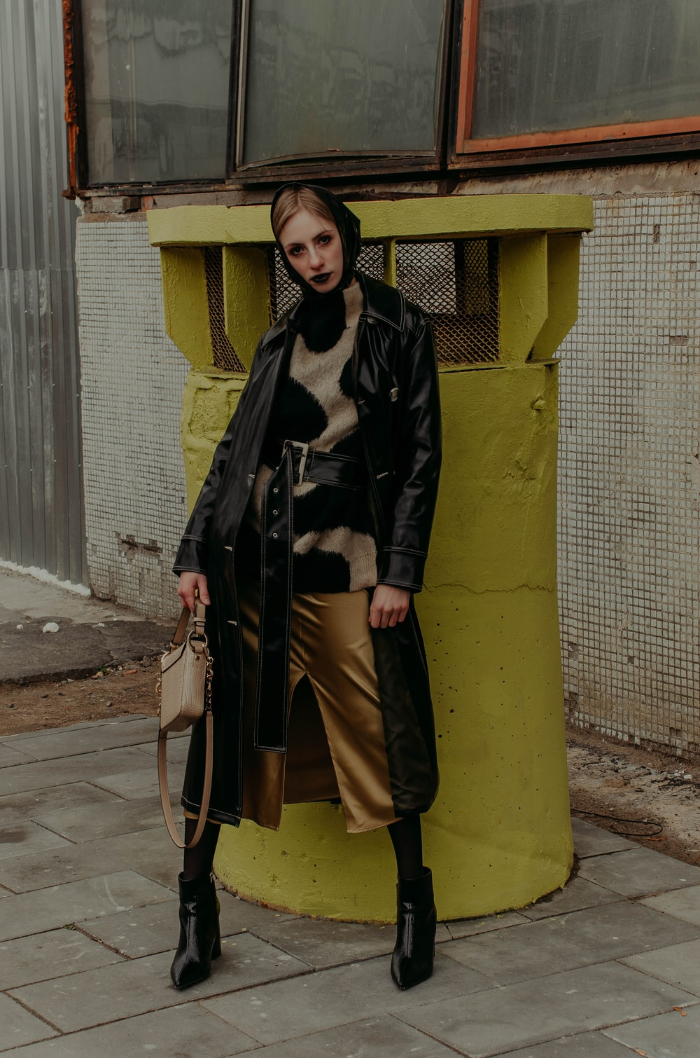woman in black coat and gray pants standing beside yellow concrete wall