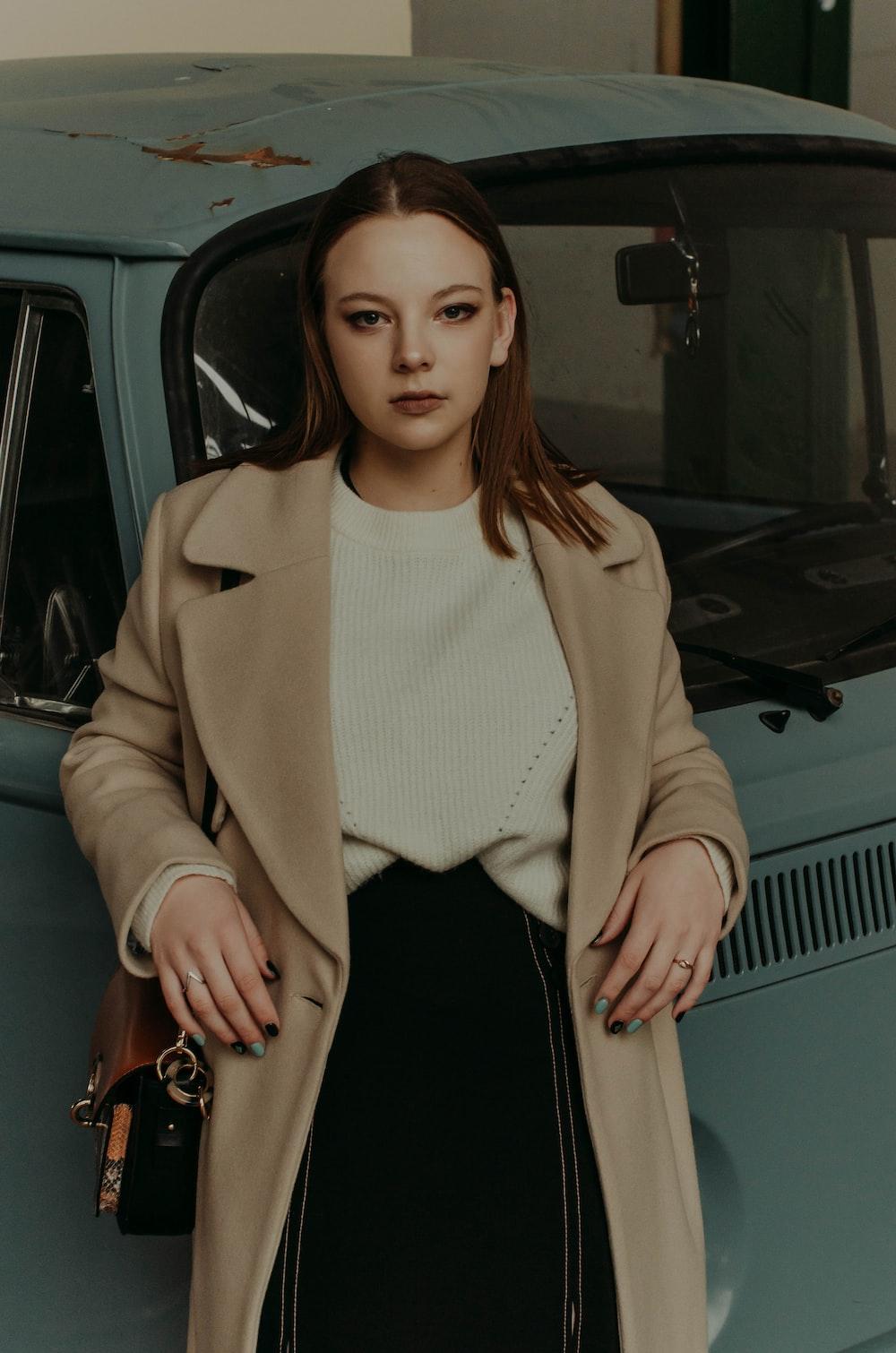 woman in beige coat standing beside car