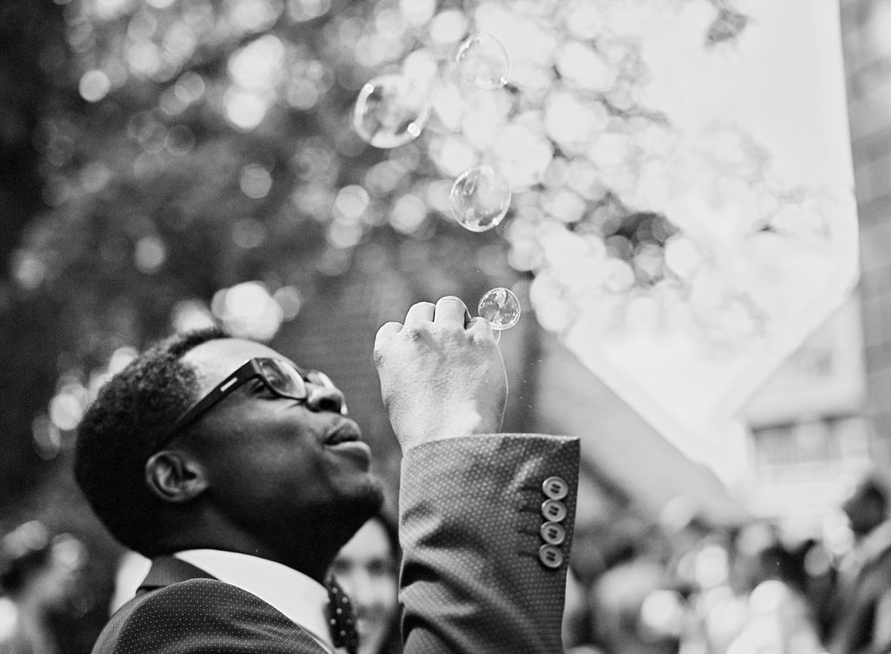 man in black suit jacket and black sunglasses blowing bubbles