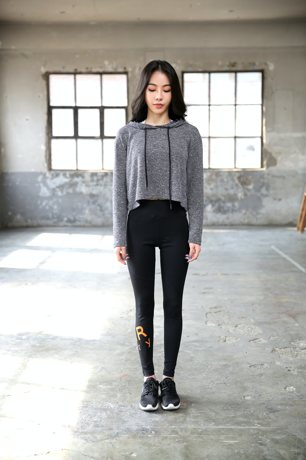 woman in gray sweater and black pants standing on gray concrete floor