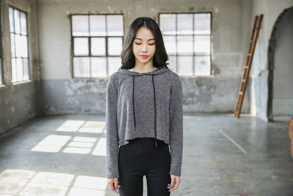 woman in gray sweater and black pants standing on gray concrete floor during daytime