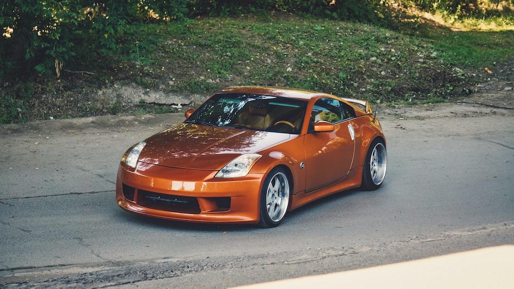 orange porsche 911 parked on gray asphalt road during daytime
