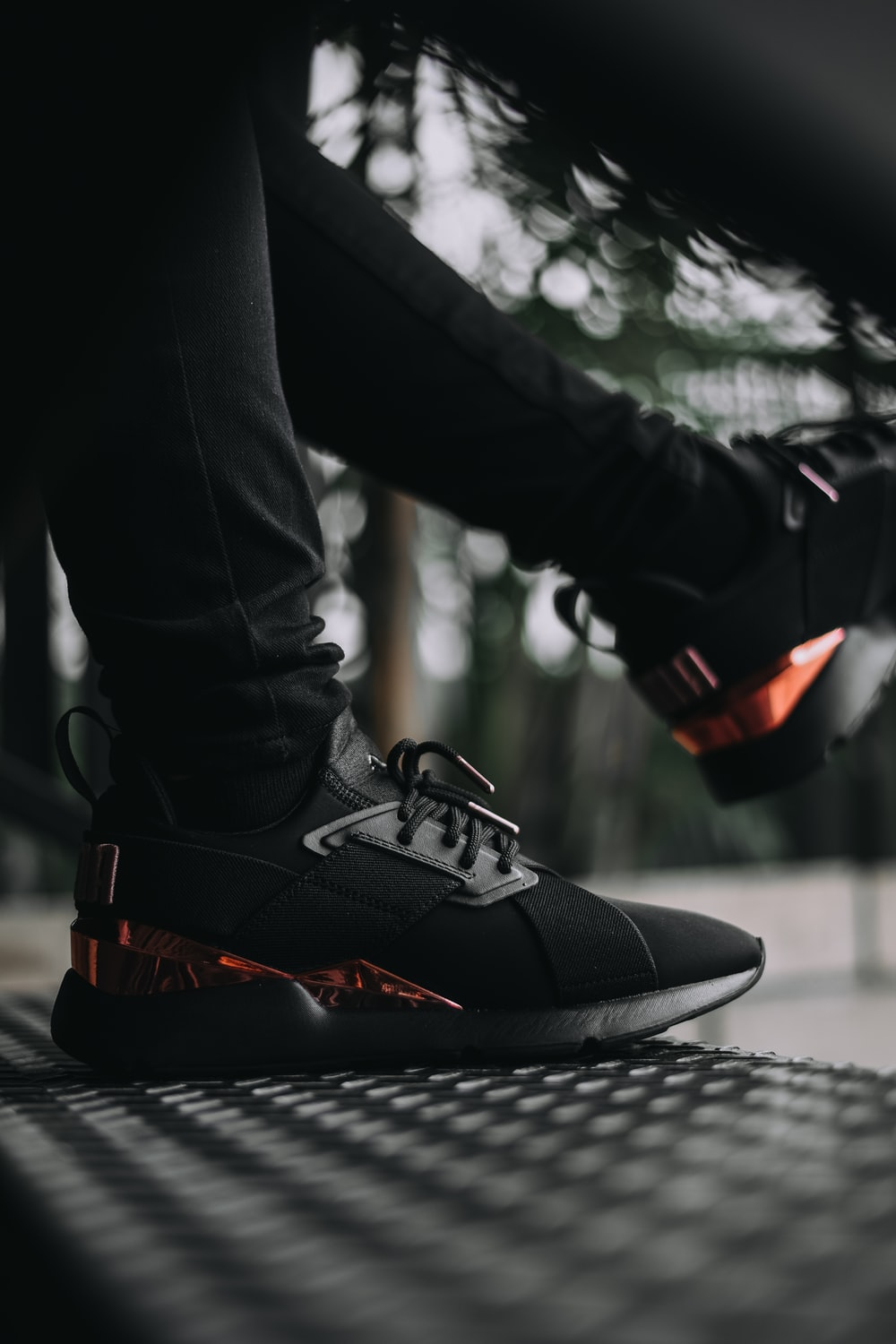 person in black pants and black and orange nike sneakers