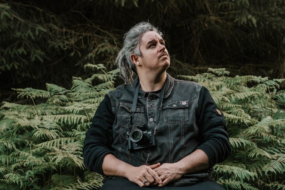 man in black jacket sitting on grass