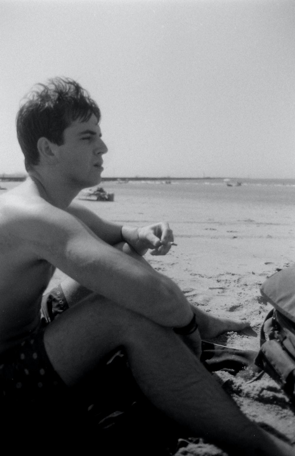 topless boy sitting on beach shore