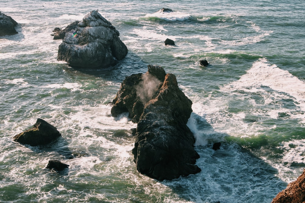 black rock formation on sea during daytime