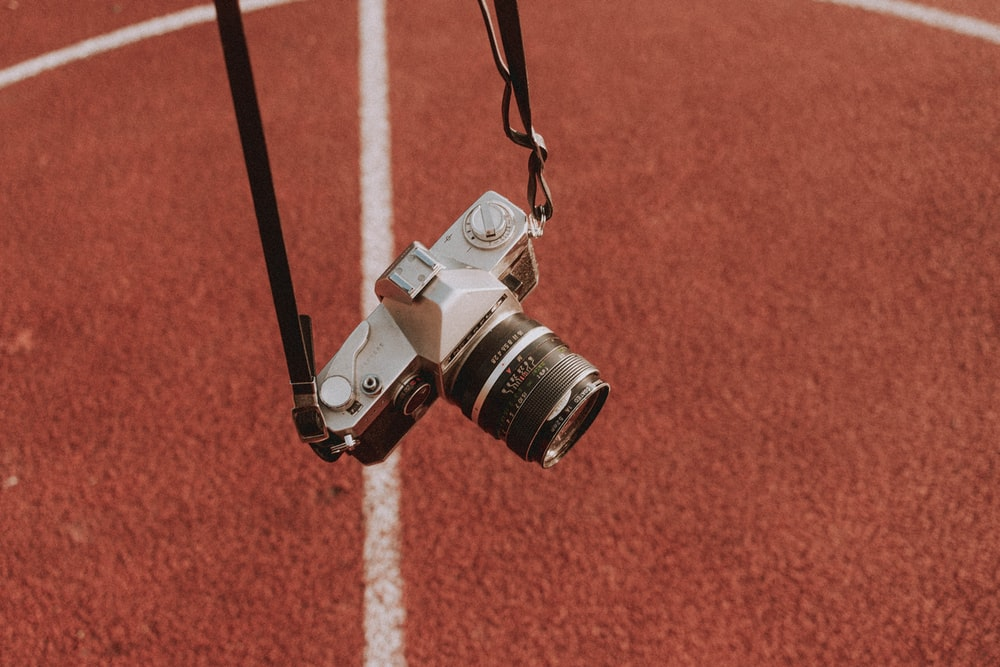 black and silver dslr camera on brown surface
