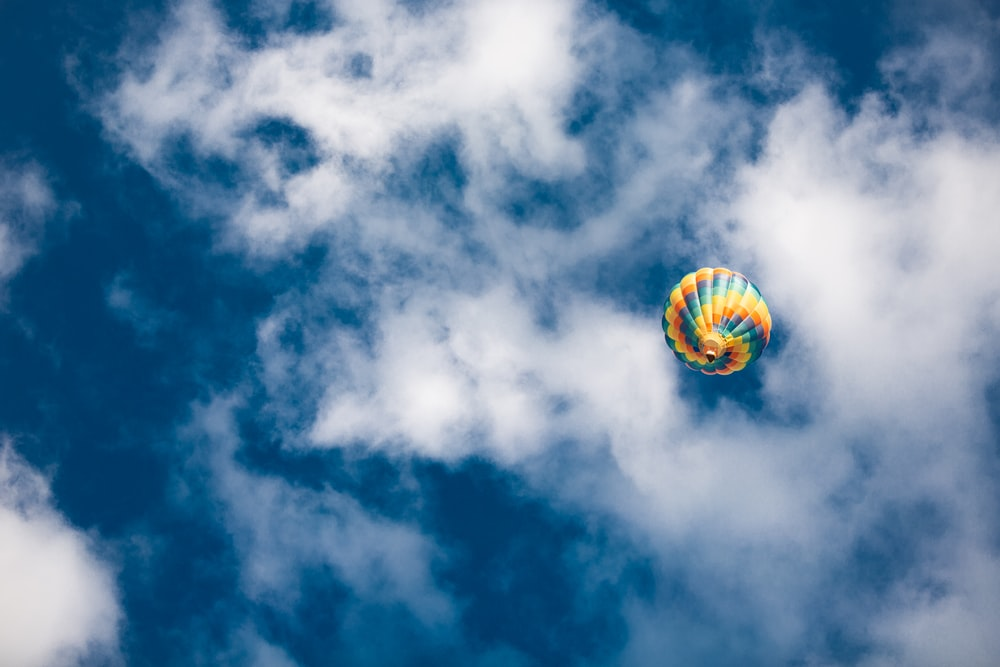 yellow green and red hot air balloon in mid air under blue and white cloudy sky