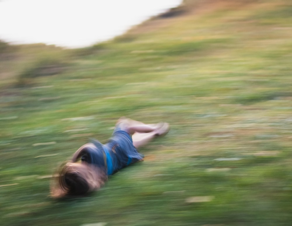 woman in green shirt lying on green grass field during daytime