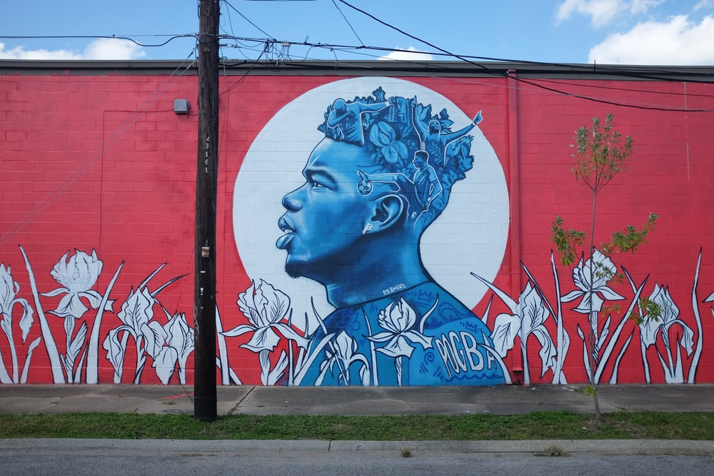 blue and white woman face graffiti on red wall