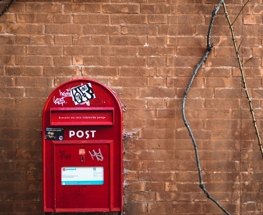 red mail box mounted on brown brick wall