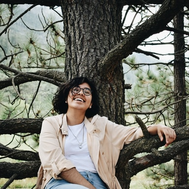 woman in white dress shirt sitting on brown tree branch during daytime