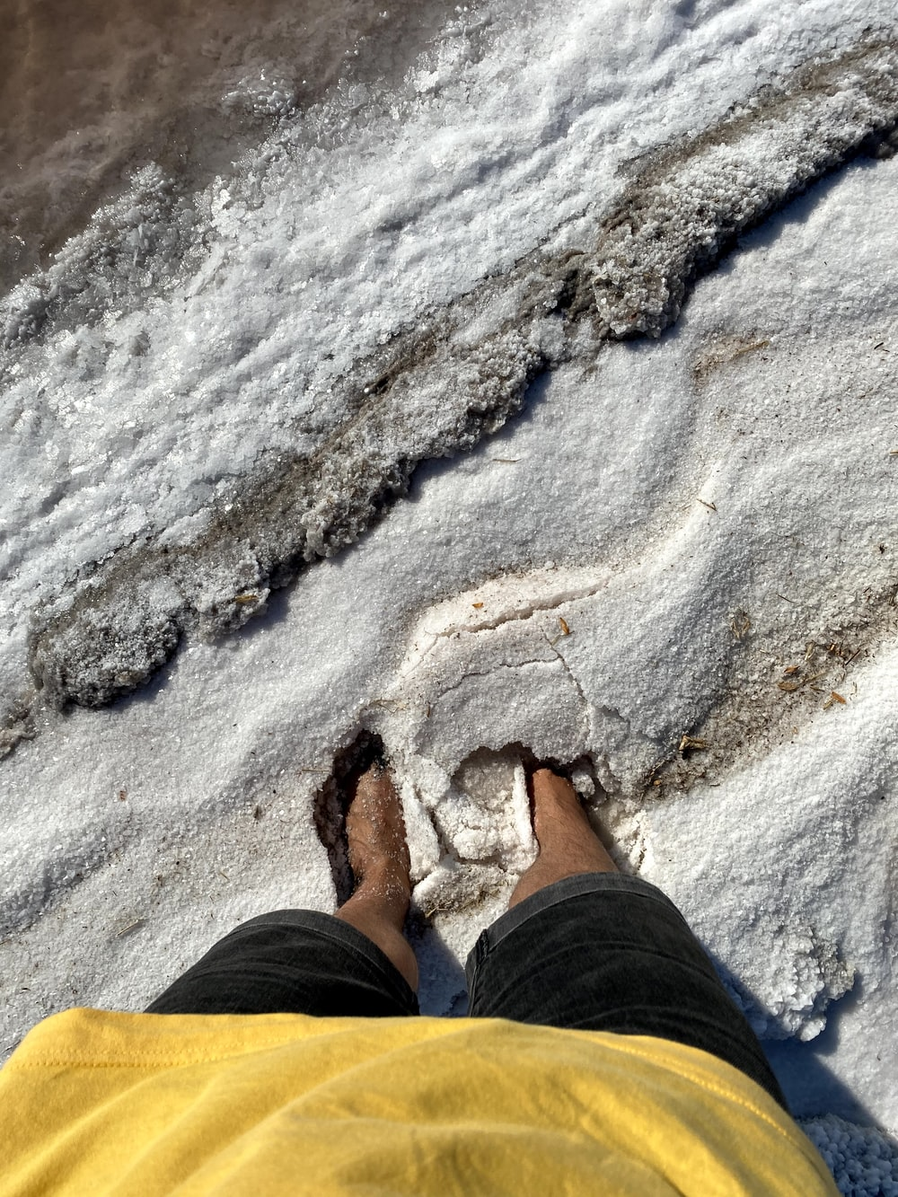 person in black pants and brown shoes standing on white sand during daytime