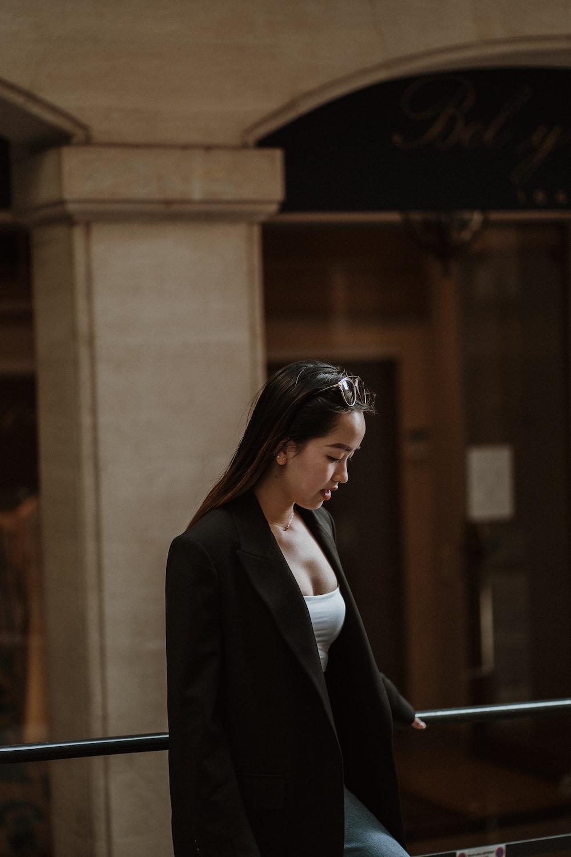 woman in black blazer standing near brown concrete building during daytime