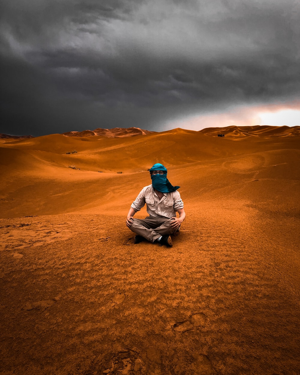 man in gray jacket sitting on brown sand under gray cloudy sky during daytime