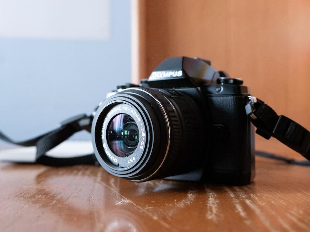 black nikon dslr camera on brown wooden table