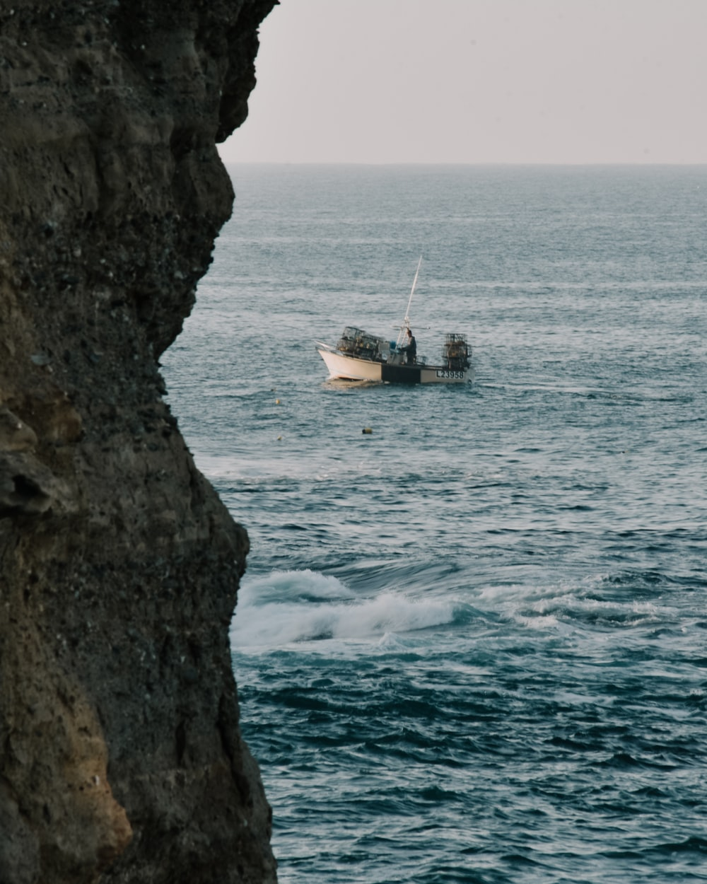 white boat on sea beside brown rock formation during daytime