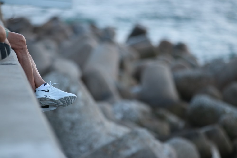 white and black nike sneakers on rocky shore during daytime