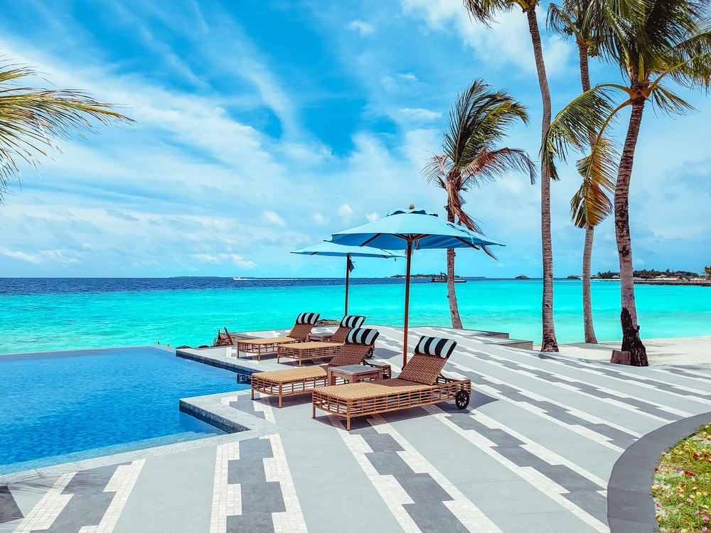 brown wooden lounge chairs on beach during daytime