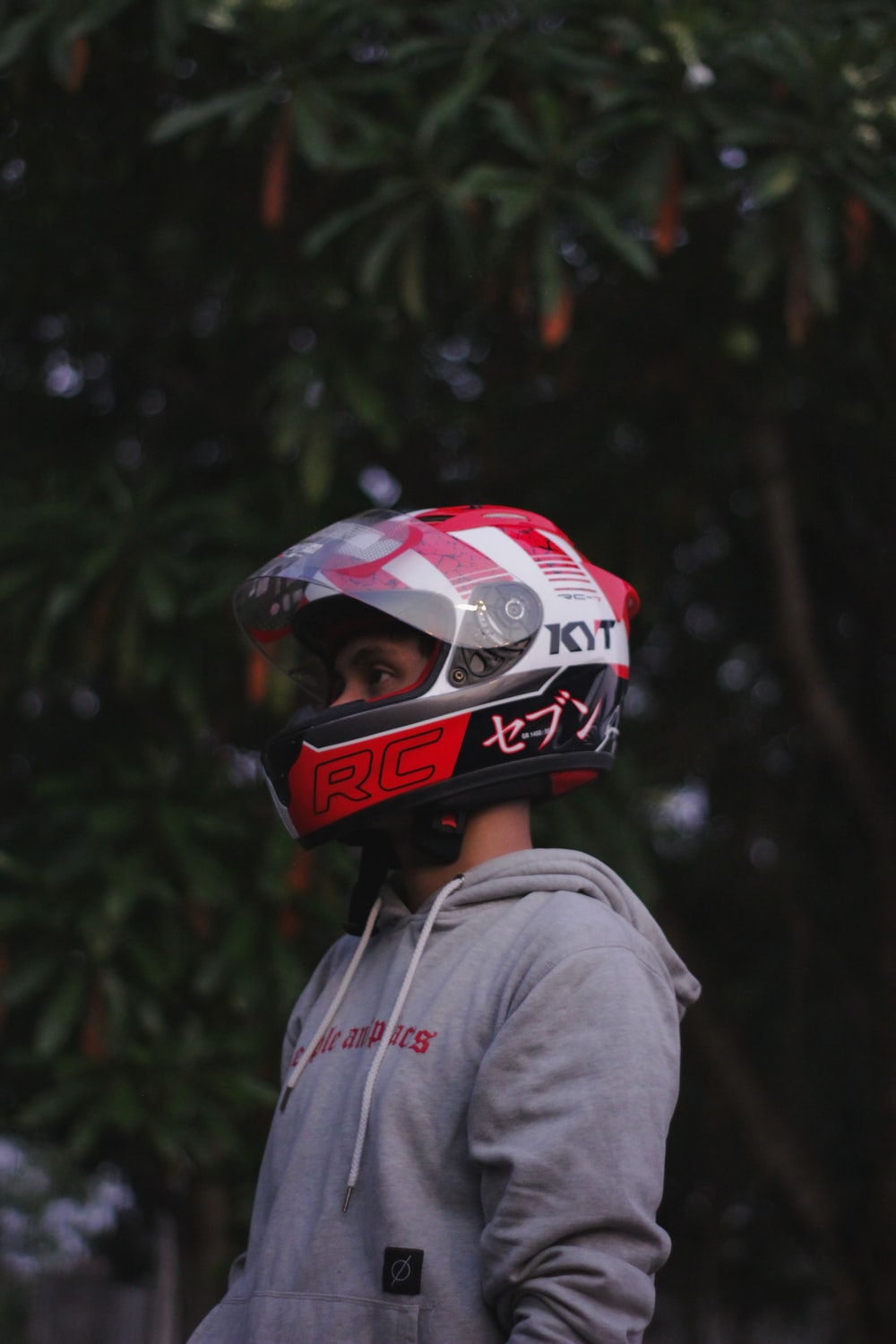 person in gray hoodie wearing red white and black helmet