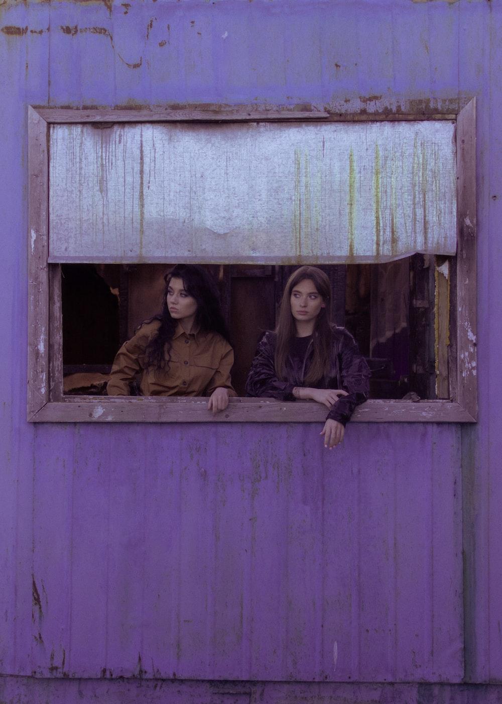 2 women sitting on window