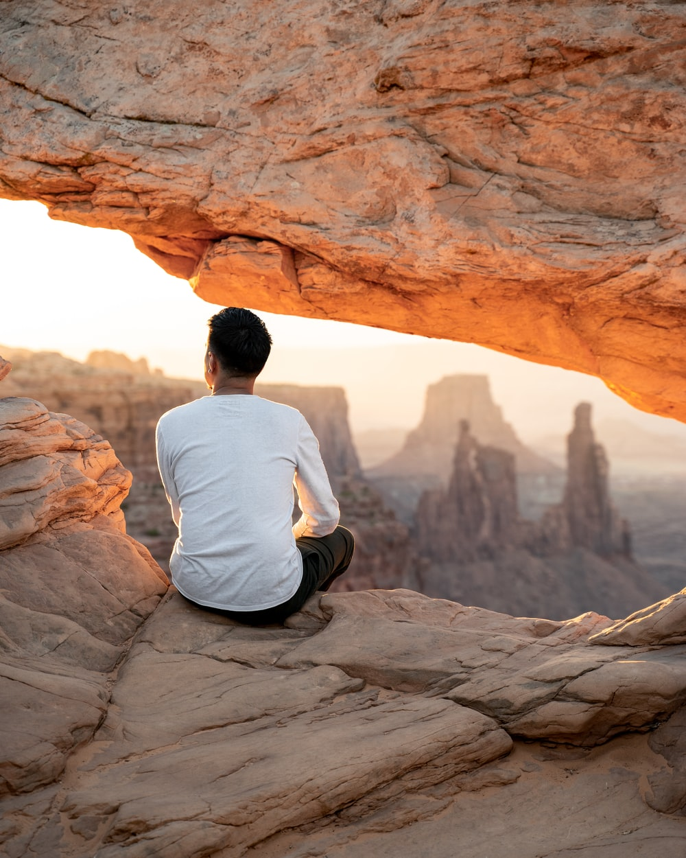 man in white shirt sitting on brown rock formation during daytime