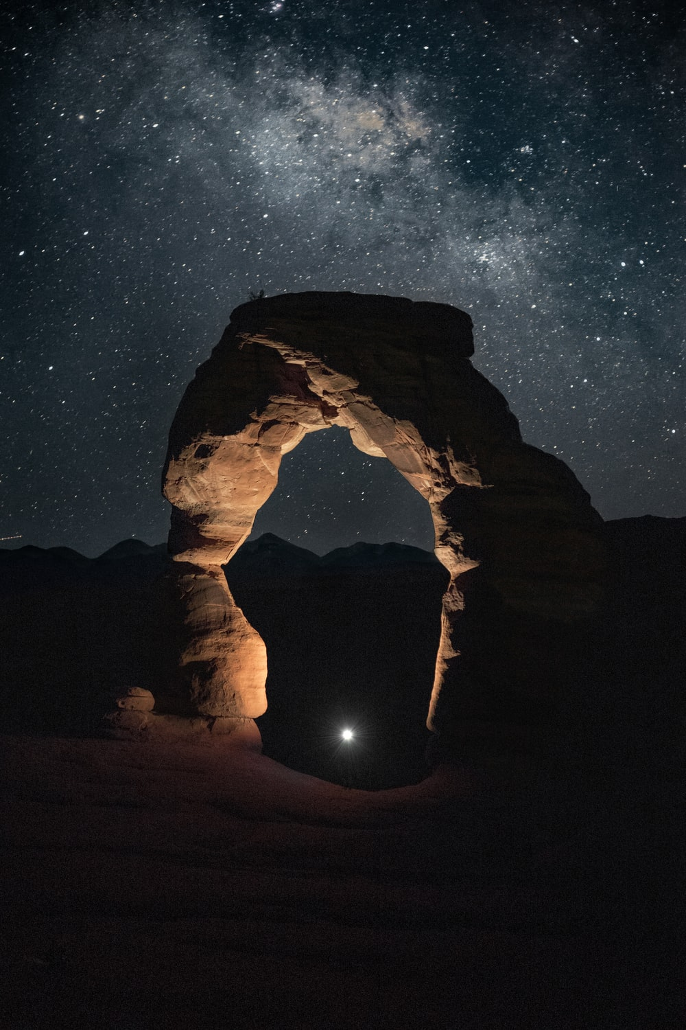 silhouette of man standing on rock formation during night time