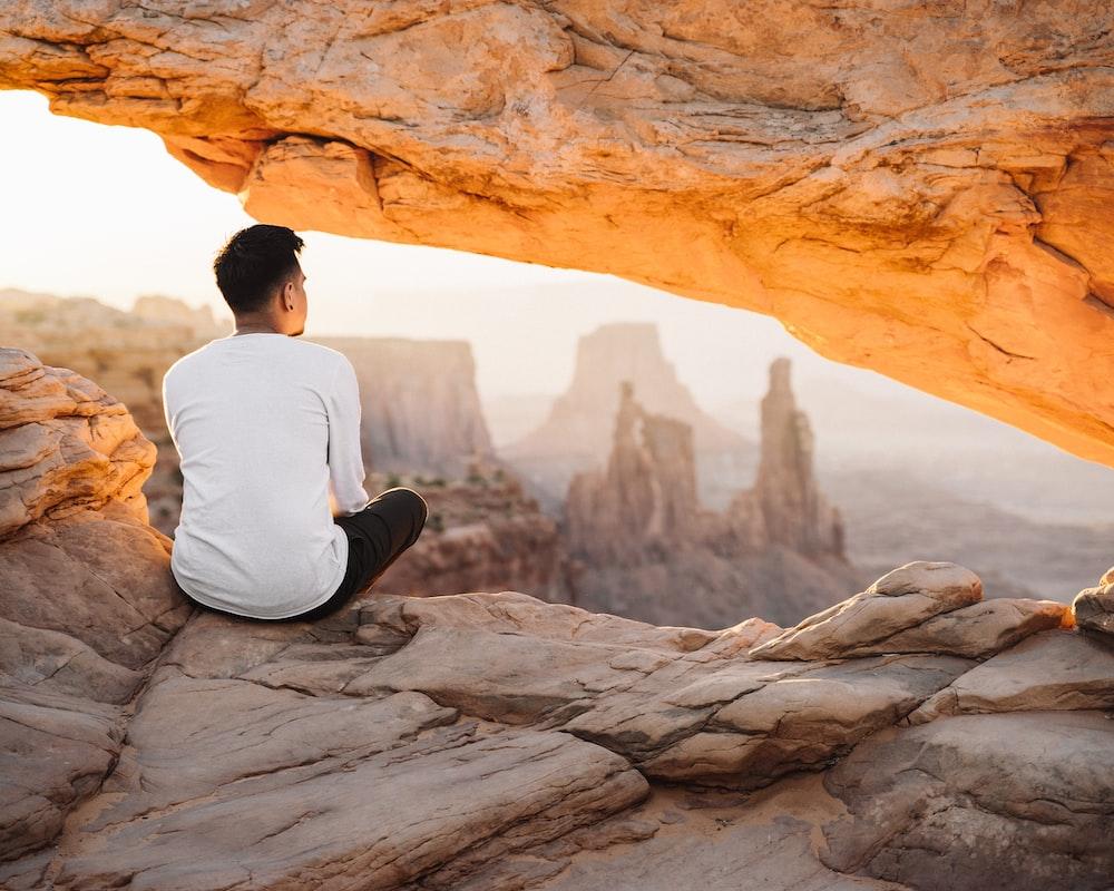 man in white long sleeve shirt sitting on rock during daytime