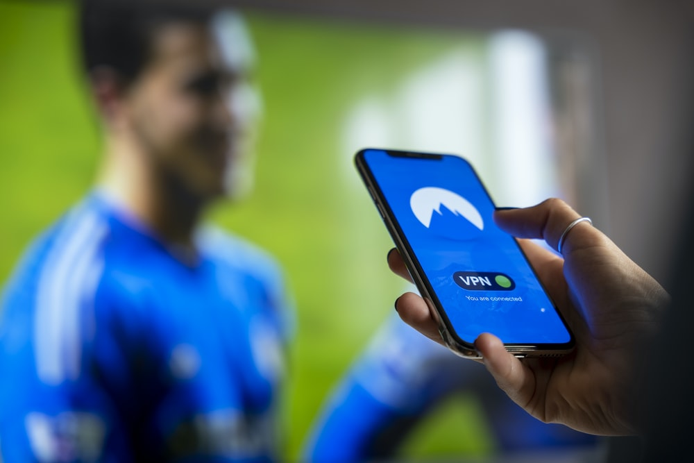 man in blue and white crew neck shirt holding black smartphone